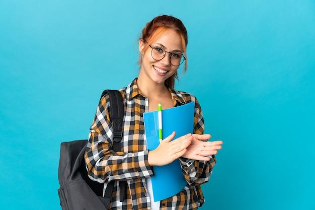 Nastoletnia studentka rosyjska dziewczyna na białym tle na niebieskim tle brawo po prezentacji na konferencji