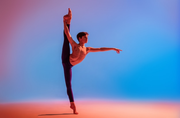 Nastoletnia tancerka baletowa tańczy boso w kolorowym świetle.