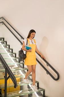 Nastoletnia uczennica chodzi na dół z książką