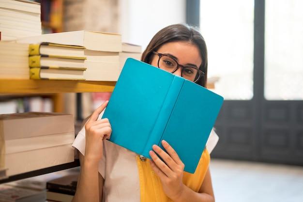Nastoletnia uczennica chuje twarz za książką