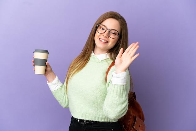 Nastoletnia uczennica na odosobnionym fioletowym tle pozdrawiająca ręką ze szczęśliwym wyrazem twarzy