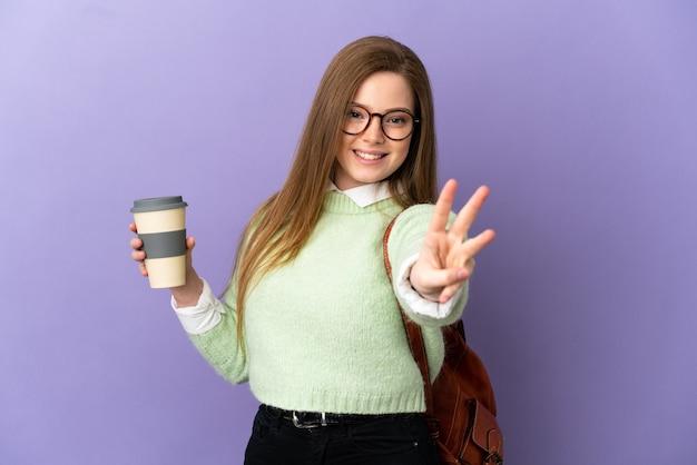 Nastoletnia uczennica na odosobnionym fioletowym tle szczęśliwa i licząca trzy palcami