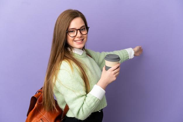Nastoletnia uczennica na odosobnionym fioletowym tle, wyciągając ręce do boku, zapraszając do przyjścia