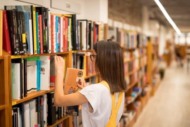 Nastoletnia uczennica podnosi książkę z półki