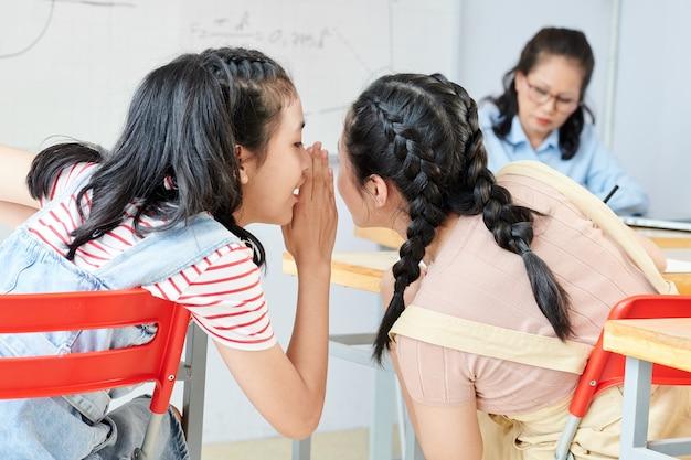 Nastoletnia wietnamska uczennica szepcząca do ucha właściwą odpowiedź swojej koleżance z klasy