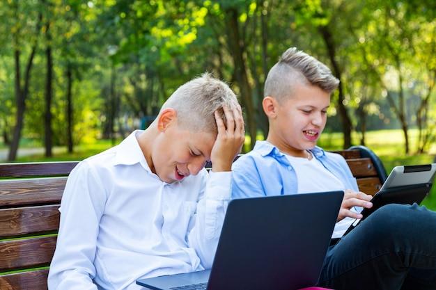 Nastoletnich chłopców na ławce w parku za pomocą laptopa i cyfrowego tabletu.