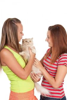 Nastoletnie dziewczyny bawić się z kotem odizolowywającym na bielu