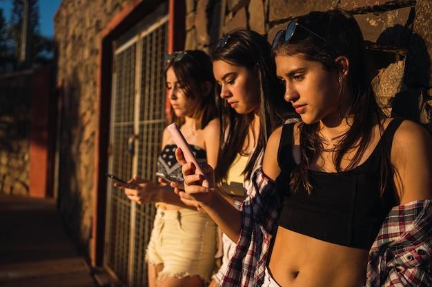 Nastoletnie dziewczyny opierające się o ścianę, patrząc na telefony komórkowe i wysyłające sms-y ze swoich smartfonów