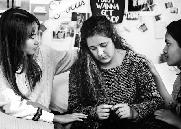 Nastoletnie dziewczyny pocieszają swojego przygnębionego płaczącego niespokojnego przyjaciela