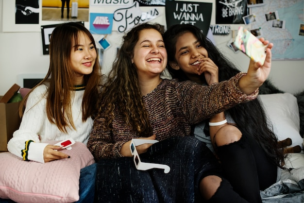 Nastoletnie dziewczyny używają smartphone brać selfie w sypialni