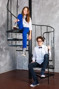 Nastoletnie dziewczyny w okularach i trampkach siedzą na spiralnych schodach w mieszkaniu na poddaszu nastolatki...