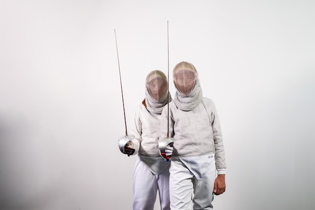 Nastoletnie dziewczyny w strojach szermierki z mieczami w ich rękach na białym tle na tle białego studia. młodzi ludzie ćwiczą i ćwiczą szermierkę. sport, zdrowy styl życia.