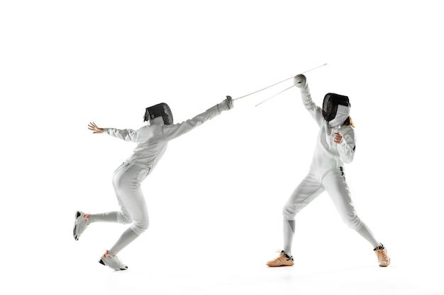 Nastoletnie dziewczyny w strojach szermierki z mieczami w rękach na białym tle na ścianie białego studia