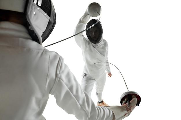 Nastoletnie dziewczyny w strojach szermierki z mieczami w rękach na białym tle na tle białego studia. młode modelki ćwiczą i trenują w ruchu, akcji. copyspace.