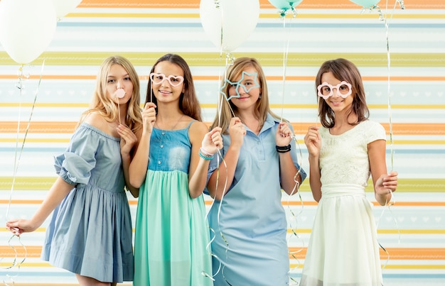 Nastoletnie dziewczyny w sukienkach stojące razem z balonami