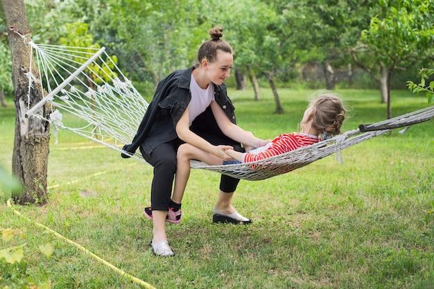 Nastoletnie siostry i dziecko bawią się na hamaku w ogrodzie przydomowym, szczęśliwe śmiejące się dziewczyny
