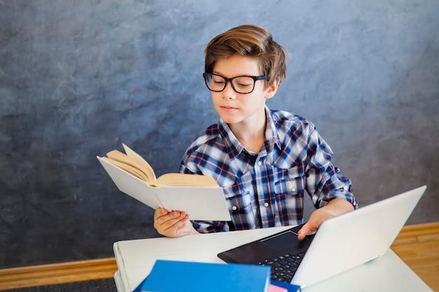 Nastoletniej chłopiec czytelnicza książka i use laptop w domu