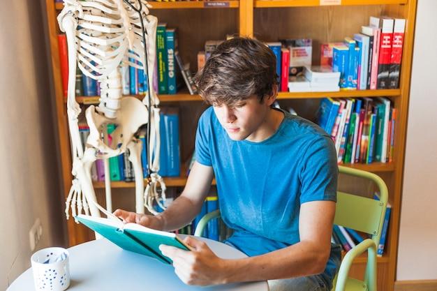 Nastoletniej chłopiec czytelnicza książka przy biblioteka stołem