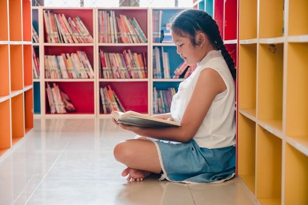 Nastoletniej dziewczyny czytelnicza książka w bibliotece edukaci i piśmienności pojęcie
