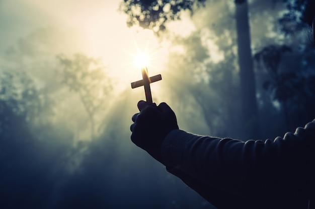 Nastoletniej dziewczyny modlenie z krzyżem w pogodnej naturze.