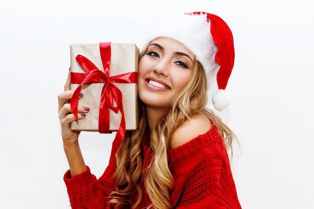 Nastrój noworoczny lub wigilijny. blond atrakcyjna dziewczyna w maskaradowym kapeluszu trzyma pudełka na prezent radosny nastrój.