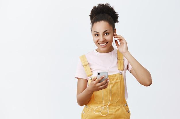 Nastrój świetne wibracje. piękna szczęśliwa afroamerykanka w żółtym kombinezonie, zakładająca słuchawki, trzymająca smartfon, wybierająca piosenkę na wyjście i spacer po ulicach miasta