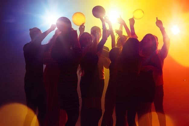 Nastrój. tłum ludzi w sylwetce podnosi ręce na parkiecie na neonowym tle. życie nocne, klub, muzyka, taniec, ruch, młodzież. żółto-niebieskie kolory i poruszające dziewczyny i chłopcy.