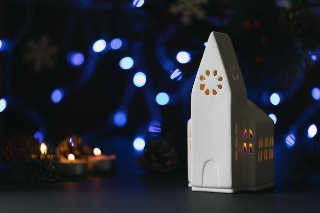Nastrojowa kompozycja świąteczna lub noworoczna z białymi ceramicznymi świecami kościelnymi, szyszkami, świecami, gałązkami jodły i girlandą.