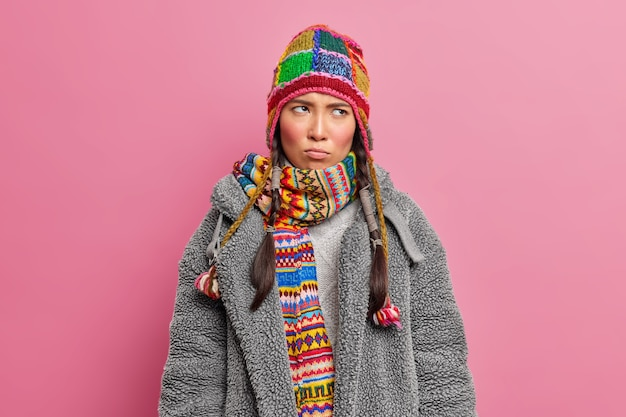 Nastrojowa niezadowolona azjatka skoncentrowana gdzieś z urażoną miną nosi szalik z dzianiny i szare futro w pozach na różowej ścianie studia