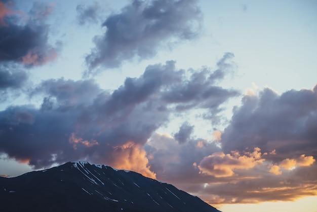Nastrojowa sceneria górska z liliowym niebem świtu. malowniczy krajobraz z rozświetlonym zachodem słońca w górach. piękny wschód słońca w górach w pastelowych kolorach. rozświetlający kolor w pochmurnym niebie o świcie.
