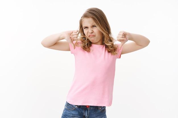 Nastrojowa, wybredna, ignorancka blond dziewczynka, pokazująca kciuki w dół, marszcząca brwi, krzywiąca się niechęć i rozczarowanie, pokazująca dezaprobatę i obrzydzenie, nie jak brokuły, stojąca zaniepokojona biała ściana