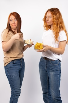 Nastrojowe kobiety w t-shirtach i dżinsach robią miny na białej ścianie trzymającej popcorn