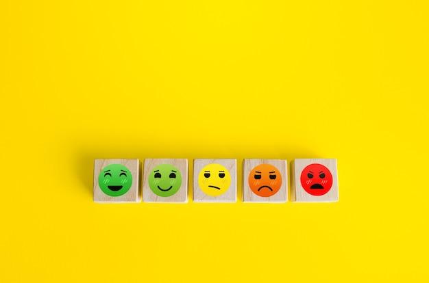 Nastrojowe twarze od szczęśliwych do złych na drewnianych klockach koncepcja recenzji oceny