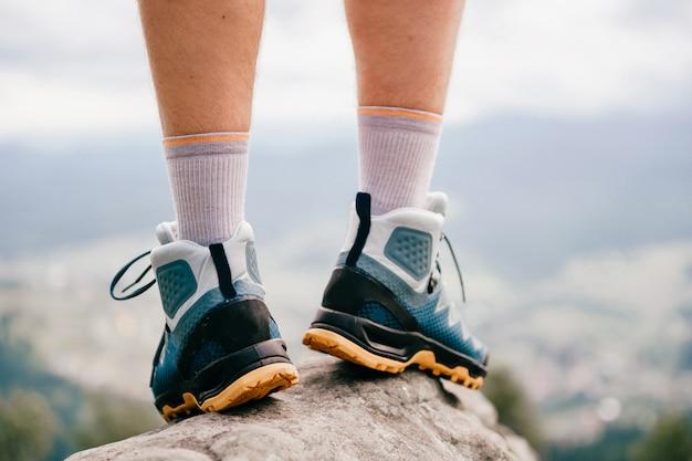 Nastrojowe zdjęcie męskich nóg noszących sportowe buty turystyczne z mocną ochronną podeszwą. męskie nogi w trekkingowym obuwiu dla halnej podróży pozyci na kamienny plenerowym przy naturą na abstrakcjonistycznym tle