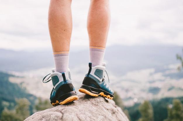 Nastrojowe zdjęcie męskich nóg w sportowych butach turystycznych z mocną ochronną podeszwą.