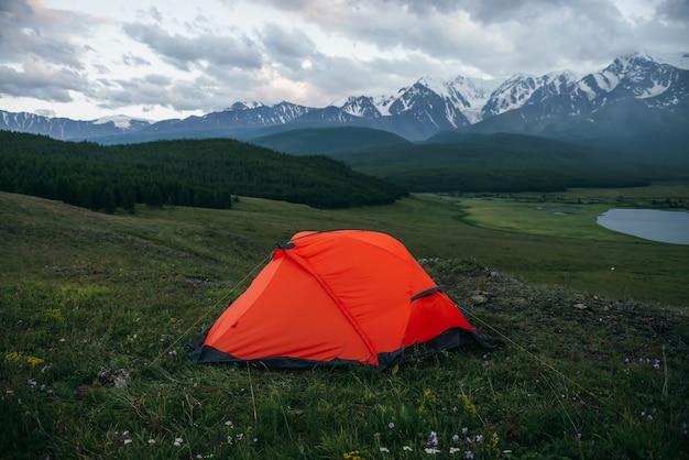 Nastrojowy krajobraz alpejski z pomarańczowym namiotem na tle jeziora i dużych ośnieżonych gór w pochmurną pogodę. niesamowita zielona sceneria z pomarańczowym namiotem z widokiem na wielkie góry pod zachmurzonym niebem.
