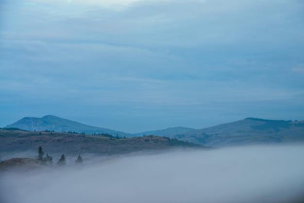 Nastrojowy krajobraz górski z zielonymi wzgórzami nad chmurami i niebieskim zachmurzonym niebem.