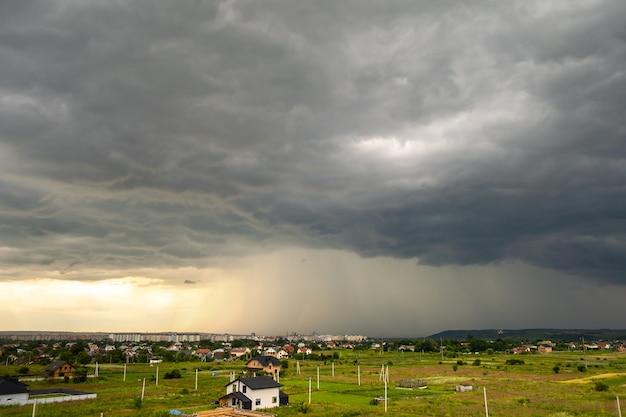 Nastrojowy krajobraz z ciemnymi burzowymi chmurami i opadającym ulewnym deszczem nad odległymi miejskimi budynkami latem.