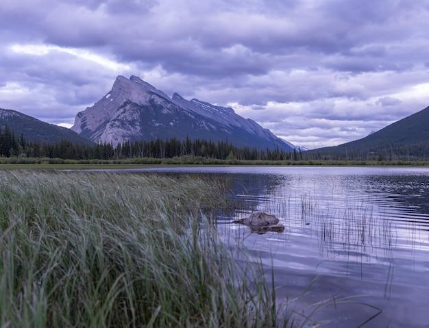 Nastrojowy zachód słońca w kanadyjskich górach skalistych z dominującą górą w parku narodowym banffcanada
