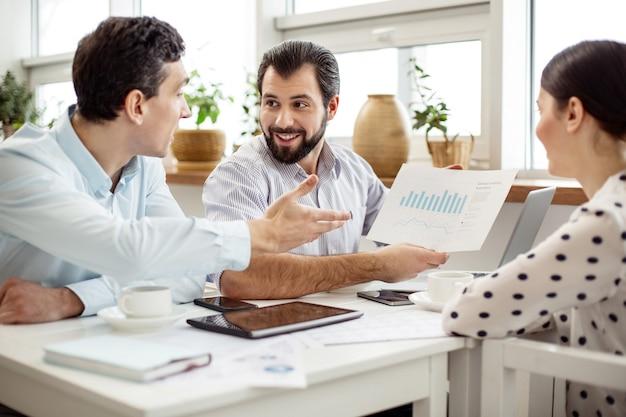 Nasz dochód. przystojny, wesoły brodaty mężczyzna trzymający kartkę papieru i pokazujący diagram siedzącym obok partnerom
