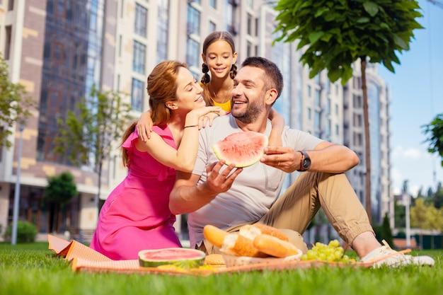 Nasz piknik. szczęśliwa miła rodzina świetnie się bawi na pikniku podczas wspólnego spędzania czasu na świeżym powietrzu