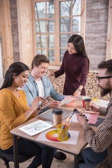 Nasz projekt. radosne, miłe, pozytywne osoby siedzące przy stole i pracujące razem skupiające się na zadaniach