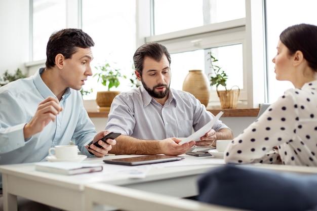 Nasz startup. przystojny, poważny brodaty mężczyzna trzymający kartkę papieru i rozmawiający ze swoimi partnerami siedzącymi obok niego