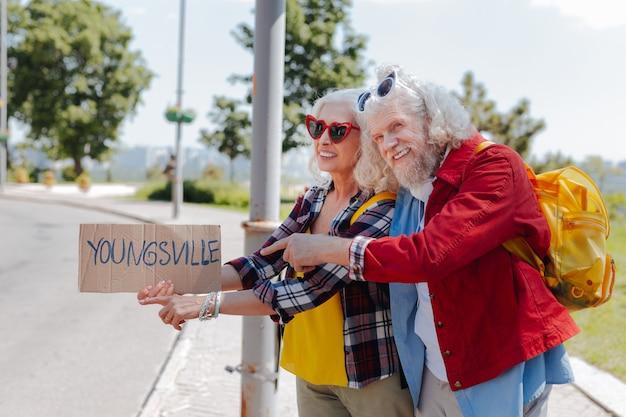 Nasz styl życia. radosna, sympatyczna para szukająca samochodu podczas wspólnej podróży