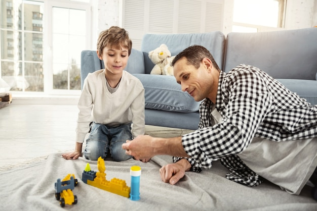 Nasz weekend. przystojny, zachwycony jasnowłosy chłopiec bawi się swoim zestawem do erekcji, a jego tata siedzi obok niego i bawi się z synem