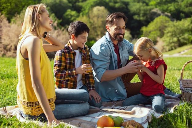 Nasz wspólny odpoczynek. zachwycona kochająca rodzina spędzająca razem czas i piknik