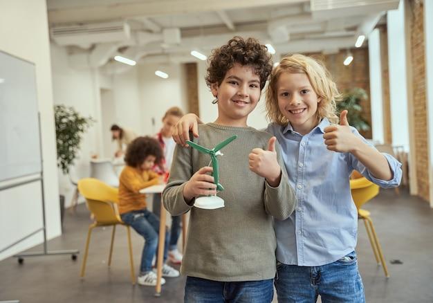 Nasz wynalazek portret dwóch szczęśliwych chłopców pokazujących kciuki do góry, trzymających mechaniczną zabawkę