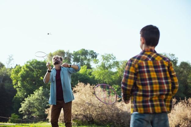 Nasz wypoczynek. skoncentrowany brodaty mężczyzna trzymający rakietę i układający badmintona z synem