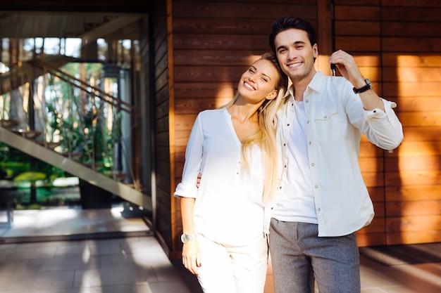 Nasz zakup. radosny szczęśliwy człowiek stojący razem ze swoją dziewczyną, pokazując klucz z domu