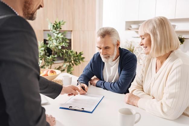 Nasza wspólna decyzja. optymistycznie zachwycona para seniorów siedząca w domu i rozmawiająca z doradcą finansowym przy podpisywaniu umowy